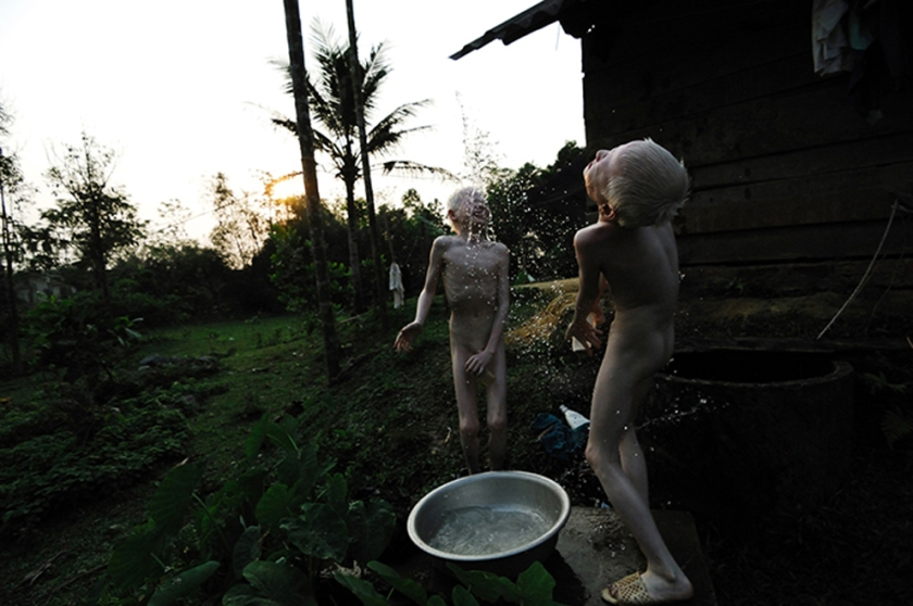 Albino twins bathing behind house