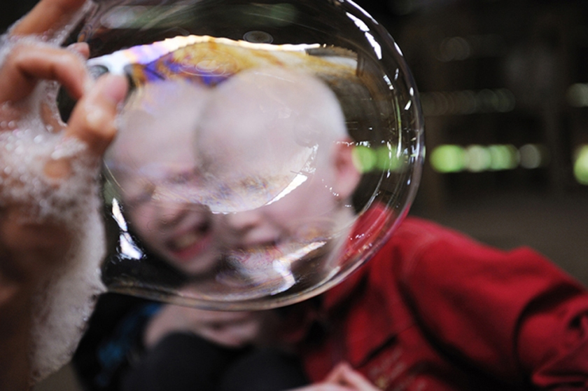 Albino twins playing with soap bubble