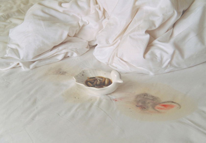 Dirty ashtray on white bedsheets