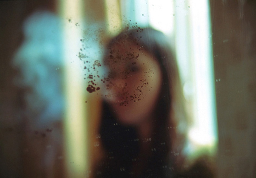Woman behind dirty window. From the 'Bees' project by Zhe Chen.
