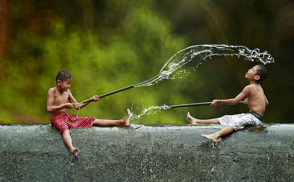 Indonesian boys having water fight