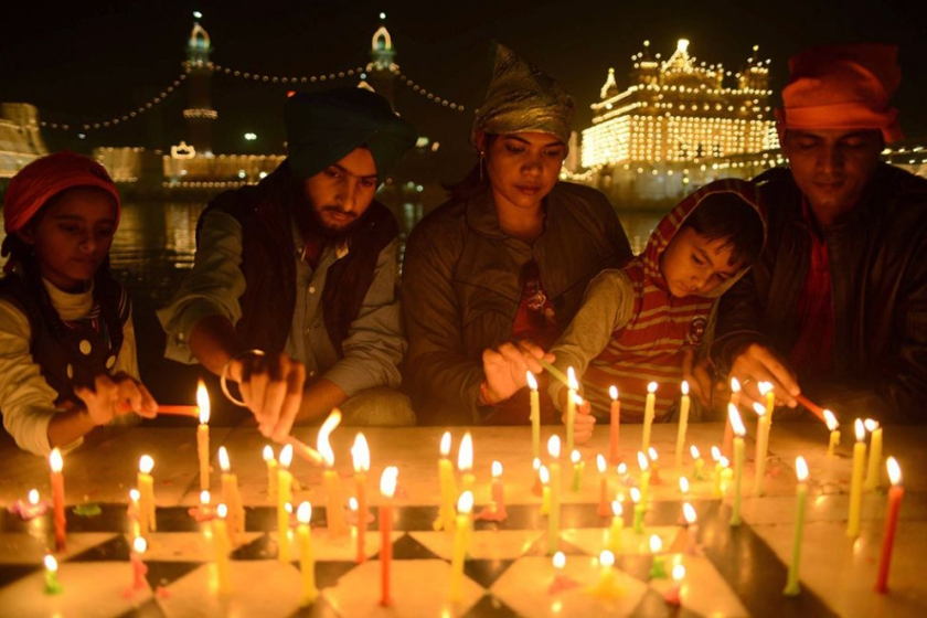 People lighting candles at riverside during Diwali