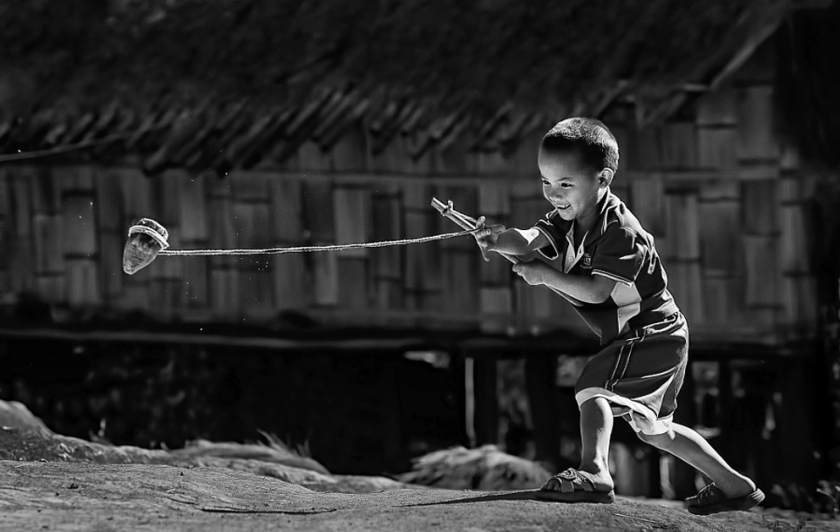 Boy playing with top